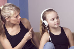 Beautiful woman is scolding her teenage daughter, girl is listening to music in headphones and ignoring her mom stock photos