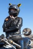 Beautiful woman scooter driver portrait against blue sky, dressed black leather outfit and helmet with yellow ears, mask is on. Her face royalty free stock photography