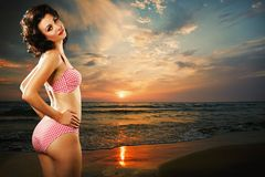 Beautiful woman on the sea beach at sunset Stock Photos
