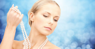 Beautiful woman with sea pearl necklace over blue Royalty Free Stock Images