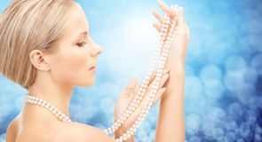 Beautiful woman with sea pearl necklace over blue royalty free stock photography