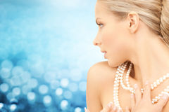 Beautiful woman with sea pearl necklace over blue royalty free stock photos