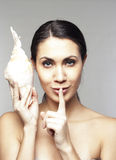 Beautiful woman with sea-shell saying shh Royalty Free Stock Photography