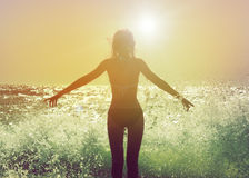 Beautiful Woman in the Sea Waves Rear View stock photo