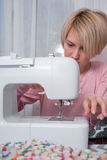 Beautiful woman seamstress sew on the sewing machine clothes. Stock Photography
