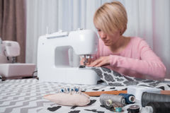 Beautiful woman seamstress sew on the sewing machine clothes. Royalty Free Stock Photos