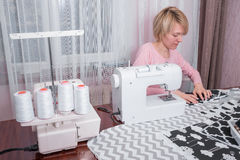 Beautiful woman seamstress sew on the sewing machine clothes. Stock Image