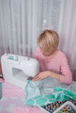 Beautiful woman seamstress sew on the sewing machine clothes. Royalty Free Stock Photo