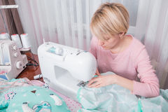 Beautiful woman seamstress sew on the sewing machine clothes. Stock Images