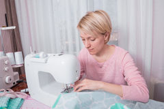 Beautiful woman seamstress sew on the sewing machine clothes. Stock Photos