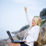 Beautiful woman on the seashore with a laptop Royalty Free Stock Images