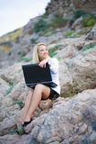 Beautiful woman on the seashore with a laptop. Portrait of woman near the sea with a laptop stock image
