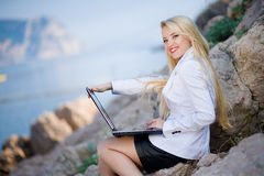 Beautiful woman on the seashore with a laptop. Portrait of woman near the sea with a laptop royalty free stock photo