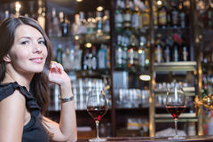 Beautiful woman seated at a bar counter Stock Photography