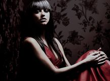 Beautiful woman seated in dark room. Beautiful woman seated in dark room Stock Photo
