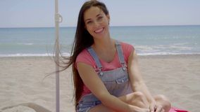 Beautiful woman seated in shade at beach. Single beautiful seated woman in pink blouse and seated under shade at beach with sand and ocean background stock footage