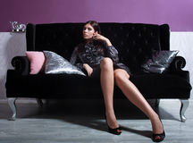Beautiful woman seated on a sofa Royalty Free Stock Photos