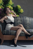 Beautiful woman seated on a sofa Royalty Free Stock Photography
