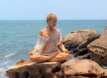 Beautiful woman seated in yoga pose at blue sea background Stock Photos