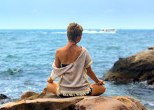 Beautiful woman seated in yoga pose at blue sea background Stock Image
