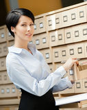 Beautiful woman seeks something in card catalog Stock Image
