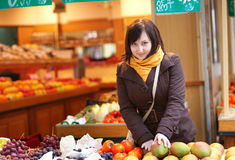 Beautiful woman selecting fresh mangoes Royalty Free Stock Images
