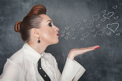 Beautiful woman send drawing hearts. On the blackboard background Stock Photography