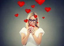 Beautiful woman sending love text message on mobile phone with red hearts flying away from screen stock photos