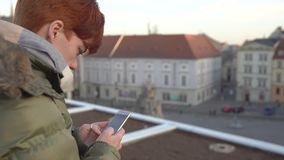 Beautiful woman is sending a text message using an app on her smartphone while sits on a promenade in the city center stock footage