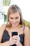 Beautiful woman sending a text sitting on a sofa Stock Photos