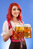 Beautiful woman serving beer at Oktoberfest. Photo of a beautiful female waitress wearing traditional dirndl and holding two mass beer steins Royalty Free Stock Photo