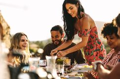 Beautiful woman serving food to friends stock images