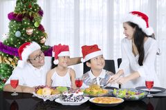 Beautiful woman serving meals for her family. Beautiful women slicing a roast turkey for her husband and children while having Christmas dinner together. Shot at stock images
