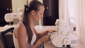 Beautiful woman sews. Powered by overlock. stock video footage