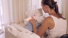 Beautiful woman sews. Powered by overlock. stock footage