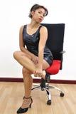 Beautiful woman black dress on desk chair stock photo