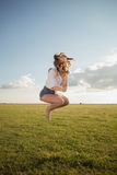 Beautiful woman with sexy legs and denim shorts jumping  on grass, shoe less Stock Photos
