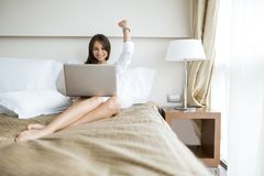 Beautiful woman with sexy long legs in shirt using a notebook in. Beautiful young woman with sexy long legs in shirt using a notebook in bed Stock Photos