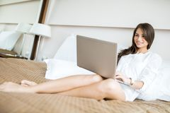 Beautiful woman with sexy long legs in shirt using a notebook in. Beautiful young woman with sexy long legs in shirt using a notebook in bed Royalty Free Stock Image