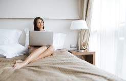 Beautiful woman with sexy long legs in shirt using a notebook in Royalty Free Stock Photography