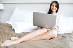 Beautiful woman with sexy long legs in shirt using a notebook in Royalty Free Stock Images
