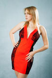 Beautiful woman in sexy red dress. Standing on blue background Royalty Free Stock Image