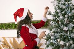 Beautiful woman in a Santa Claus costume decorate the Christmas tree decorations at home. Girl hangs a silver ball on a green stock photos