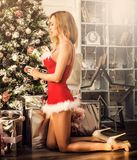 Beautiful woman in a Santa Claus costume decorate the Christmas tree royalty free stock photo