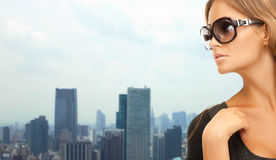 Beautiful woman in shades over city background. People, fashion, eyewear and style concept - beautiful woman in shades over city background Royalty Free Stock Photography