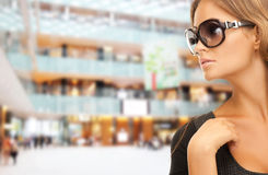 Beautiful woman in shades over mall background. People, fashion, shopping, eyewear and style concept - beautiful woman in shades over mall background Stock Image