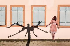 Woman with a tree shadow on the wall. Beautiful woman with the shadow of a pollarded plane tree on the wall Royalty Free Stock Photography