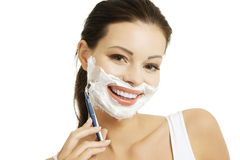 Beautiful woman shaving her face with a razor Stock Photography