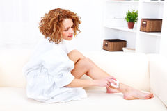 Beautiful woman shaving her legs with epilator Royalty Free Stock Photography