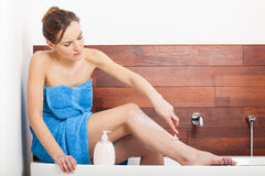 Beautiful woman shaving legs Stock Photo